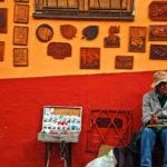 No se puede negar que Bogotá tiene una vida urbana diversa en matices y postales. Aquí un artista que no solo hace piezas únicas sino que vive del tradicional rebusque con su toldillo callejero. Foto: Jess Kraft -Shutterstock